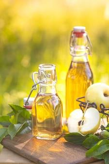 Deux bouteilles en verre de vinaigre de cidre de pomme et de pommes mûres fraîches.