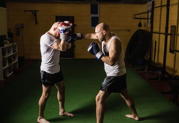 Deux boxeurs pratiquant la boxe en studio de remise en forme