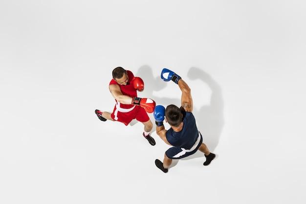 Deux boxeurs professionnels boxe isolé sur fond blanc studio, action, vue de dessus. couple d'athlètes caucasiens musclés en forme de combat.