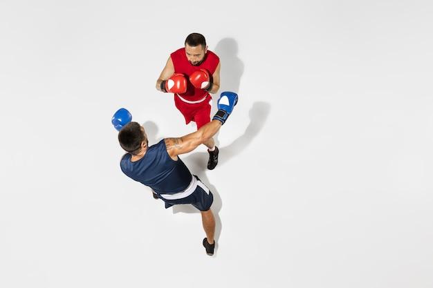 Deux boxeurs professionnels boxe isolés sur fond blanc studio, action, vue de dessus. couple d'athlètes caucasiens musclés en forme qui se battent. concept de sport, de compétition, d'excitation et d'émotions humaines.