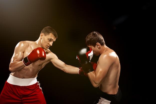 Deux boxeurs professionnels sur fond noir,