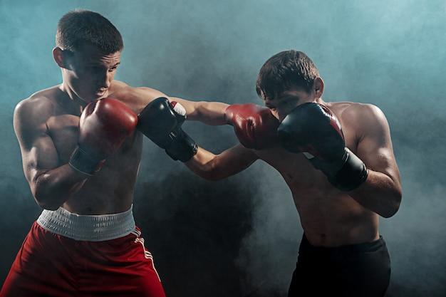 Deux boxeurs professionnels sur smoky noir,