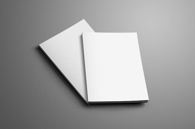 Deux brochures a4, (a5) fermées vierges avec des ombres douces et réalistes isolées sur une surface grise. l'une des brochures se trouve à un angle de la deuxième brochure.