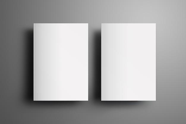 Deux brochures vierges universelles fermées a4, (a5) avec des ombres douces et réalistes isolées sur une surface grise. haut de la vue.