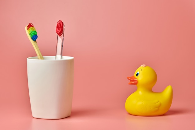 Deux brosse à dents et jouet de canard, espace de copie. outil de soins personnels pour protéger la cavité buccale, enlever la plaque et le tartre.