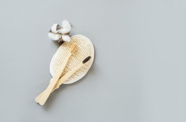 Deux brosses en bambou pour se brosser les dents, allongées sur une brosse en bambou pour le visage et une fleur de cato sur fond gris. place pour le texte