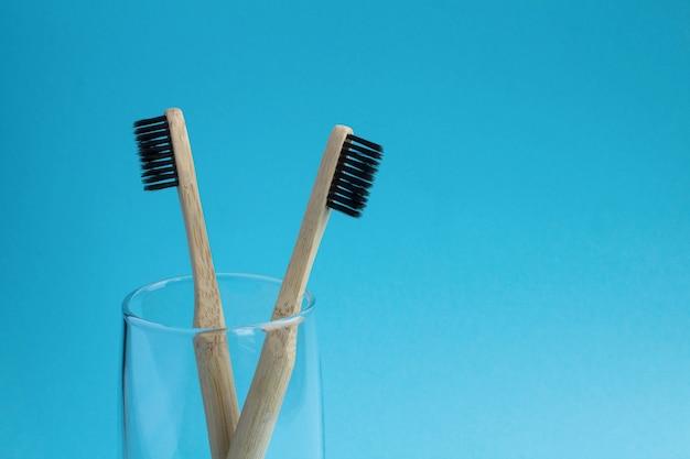 Deux brosses à dents en bambou dans le verre sur le fond bleu.copy space.closeup.