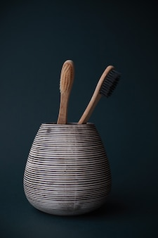 Deux brosses à dents en bambou dans un verre en porcelaine sur un fond dégradé cyan