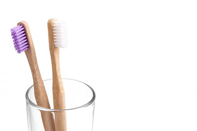 Deux brosses à dents en bambou dans un verre