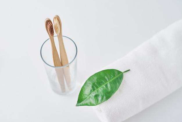 Deux brosses à dents en bambou respectueuses de l'environnement en verre et serviette sur blanc.