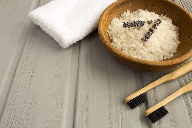 Deux brosses à dents en bambou, serviette blanche et sel de bain de mer dans le bol brun sur le gris