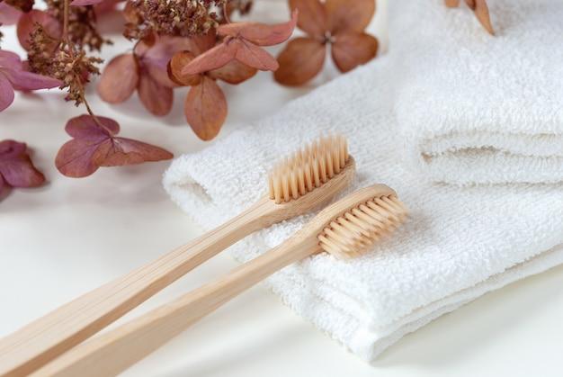 Deux brosses à dents en bambou sur des serviettes blanches avec des fleurs