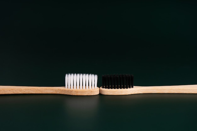 Deux brosses à dents en bois de bambou antibactériennes écologiques avec des poils blancs et noirs sur fond noir. prendre soin de l'environnement est une tendance. tolérance. copiez l'espace.