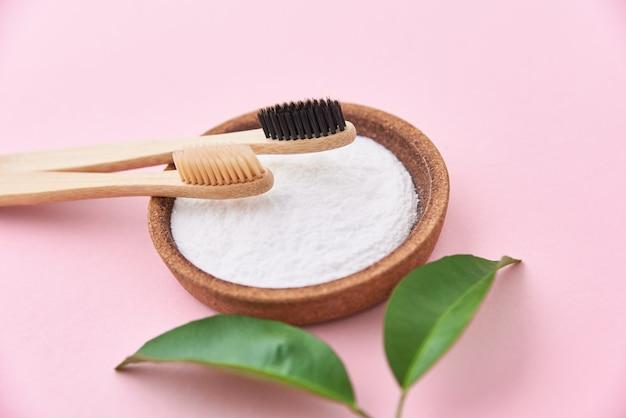 Deux brosses à dents en bois de bambou et bicarbonate de soude. brosses à dents écologiques, concept zéro déchet