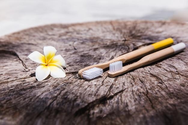 Deux brosses à dents en bois de bambou écologique blanc et jaune sur bois