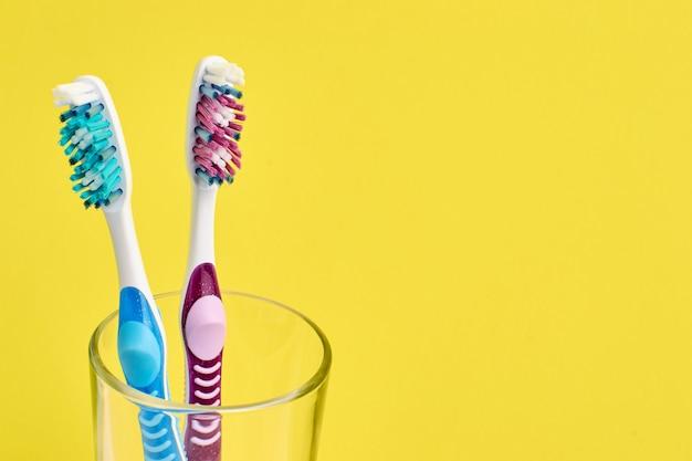 Deux brosses à dents colorées différentes dans un verre sur jaune
