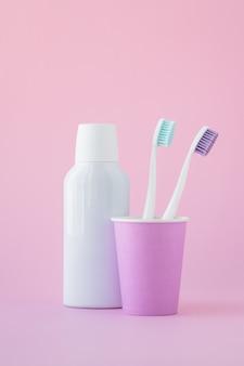 Deux brosses à dents dans une tasse rose et un rince-bouche dans une bouteille, concept d'hygiène buccale.