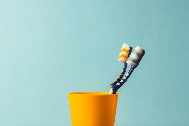 Deux brosses à dents dans un verre en plastique sur fond bleu. le concept de changer les brosses à dents, l'hygiène buccale, la dentisterie. famille jeune et sympathique.