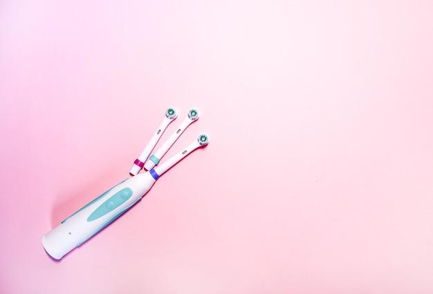 Deux brosses à dents électriques sur un fond rose clair doux.
