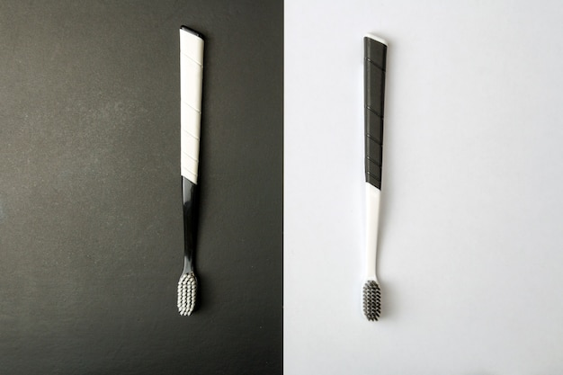 Deux brosses à dents noir et blanc sur un monochrome.