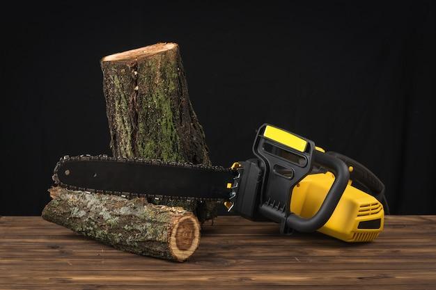 Deux bûches sciées et une tronçonneuse électrique sur un fond en bois. outil électrique pour la transformation du bois.
