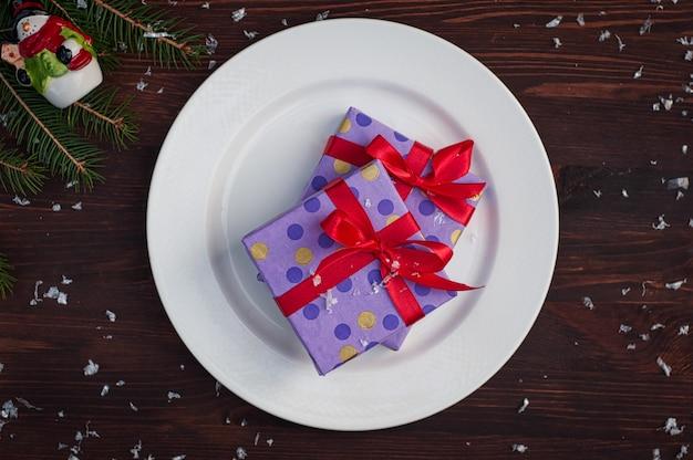 Deux cadeaux emballés dans du papier avec un ruban rouge sur une plaque blanche