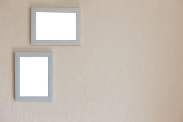 Deux cadres blancs sur un mur beige