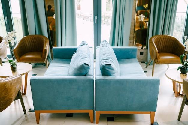 Deux canapés bleu clair face à face face à la sortie du balcon dans la salle du restaurant