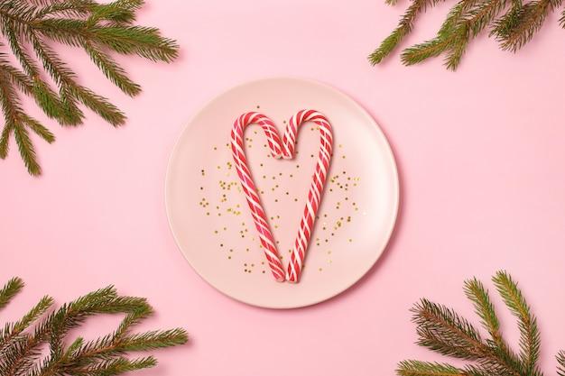 Deux cannes de bonbon en forme de coeur sur des étoiles de paillettes d'or sur une plaque rose sur fond clair.