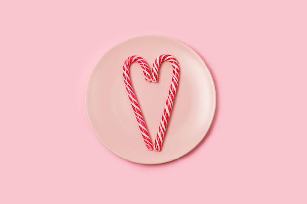 Deux cannes de bonbon en forme de coeur sur une plaque rose sur fond rose.