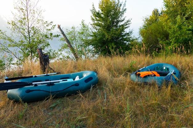 Deux canots pneumatiques avec du matériel de pêche au petit matin pendant le brouillard, garés sur les rives de la rivière.