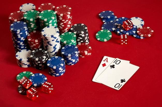 Deux cartes et jetons sur fond rouge. gros pari de l'argent du jeu. cartes - as et dix. votre distribution à table