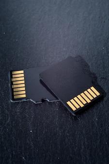 Deux cartes micro sd se superposent sur un fond texturé sombre, avec des contacts dorés en haut. fermer.