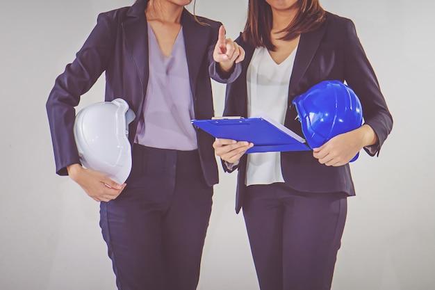 Deux casques d'ingénieurs industriels avec une tablette dans les mains