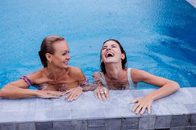 Deux, caucasien, femme, dans, bleu, piscine, à, jour pluvieux