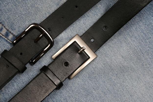 Deux ceintures en cuir noir sur fond de jeans