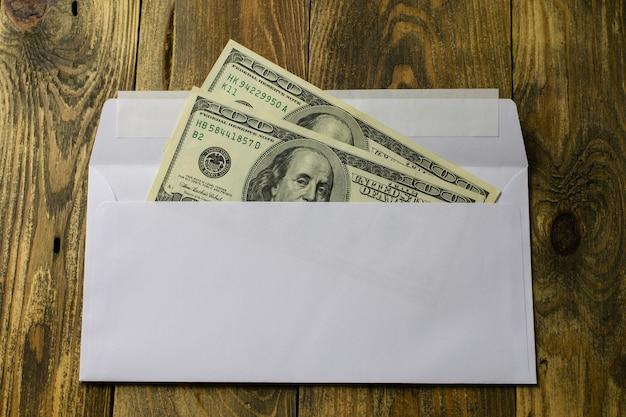 Deux cents dollars en cent dollars en espèces dans une enveloppe blanche.