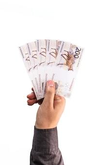 Deux cents factures de reais offertes par des mains masculines, concept de paiement.