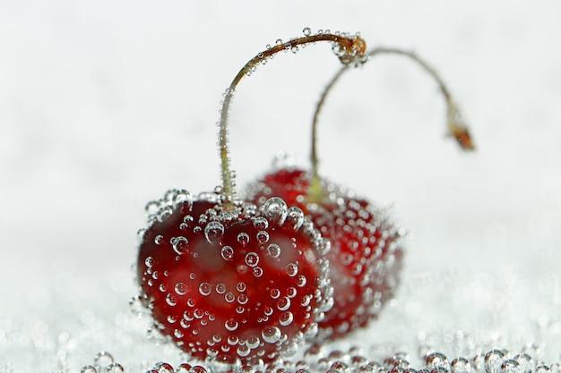 Deux cerises douces en bulles de gaz sur un rose pâle flou