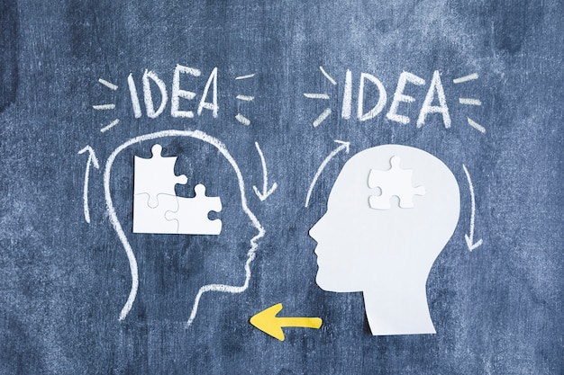 Deux cerveaux échangeant les informations avec des morceaux de puzzle et des flèches jaunes sur le tableau noir