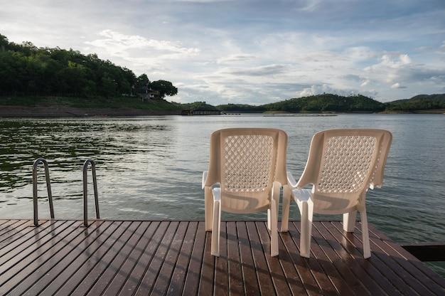 Deux chaise en plastique sur le pont flottant dans le lac le soir