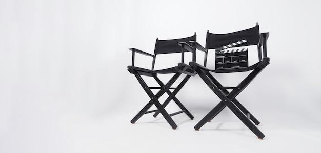Deux chaise de réalisateur noir et clap sur fond blanc.