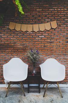 Deux chaises blanches avec une table de vases noirs et de fleurs étaient placées devant le mur de briques rouges.