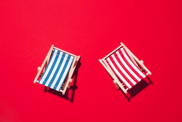 Deux chaises longues avec des ombres dures sur fond de papier rouge.