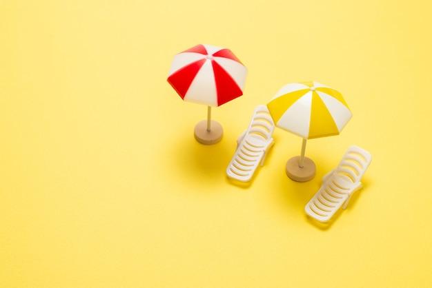 Deux chaises longues et un parapluie rouge sur fond jaune. copiez l'espace.