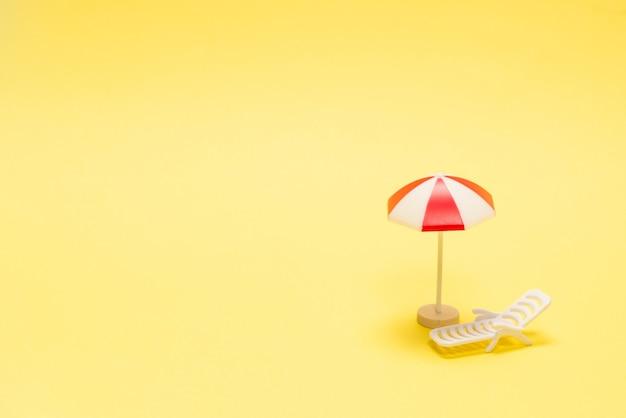 Deux chaises longues et un parasol rouge sur jaune.