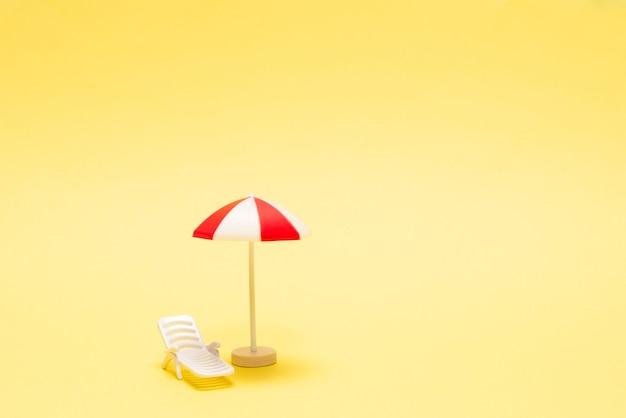 Deux chaises longues et un parasol rouge sur un jaune