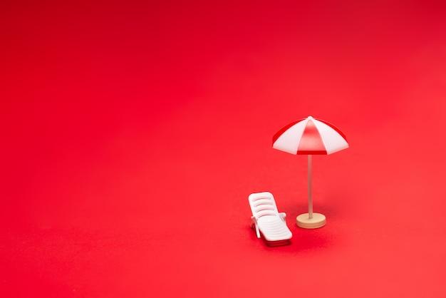 Deux chaises longues et parasols rouges sur fond rouge. espace de copie.