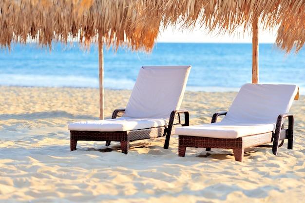 Deux chaises de plage avec parasol blanc