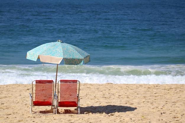 Deux chaises de plage rouges et un parasol bleu sur la plage de copacabana, rio de janeiro, brésil
